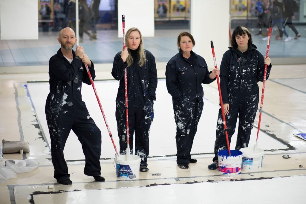 Four artists with painting overalls and paint